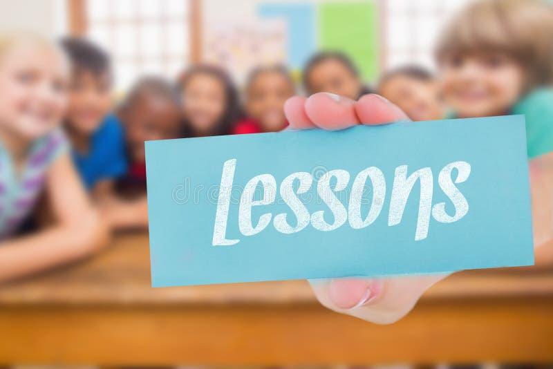 Lessen tegen leuke leerlingen die bij camera in klaslokaal glimlachen stock afbeelding