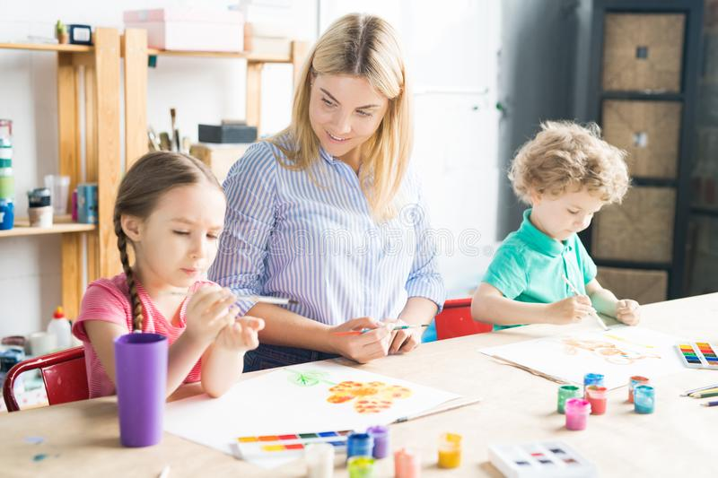 Lesson at art class. Smiling young teacher drawing with paints and teaching her pupils to paint royalty free stock photo