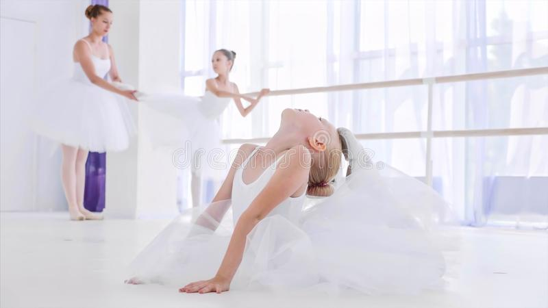 Child girl ballerina in white tutu is doing stretch exercises on ballet lesson. royalty free stock images