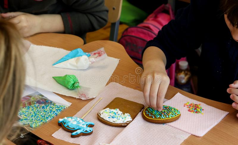 Lesson of creativity in elementary school, children learn to decorate Easter gingerbread stock image