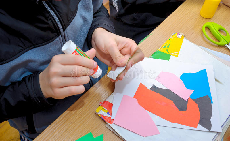 At a lesson of the fine arts. The school student does abstract application, of multi-colored sheets of paper royalty free stock photos