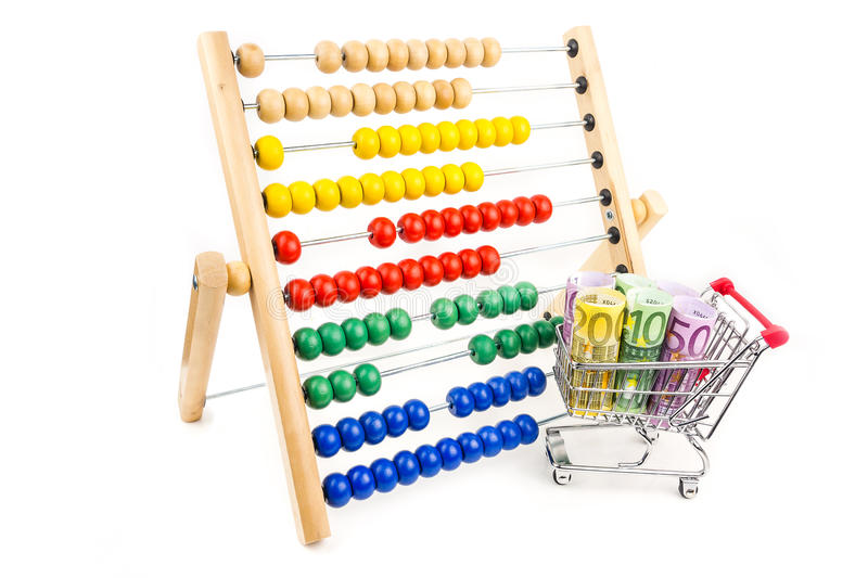 Lesson one in business. Silver shopping trolley full of euros with big wooden caunter on white background as a school equipment and help for children, teaching stock photography