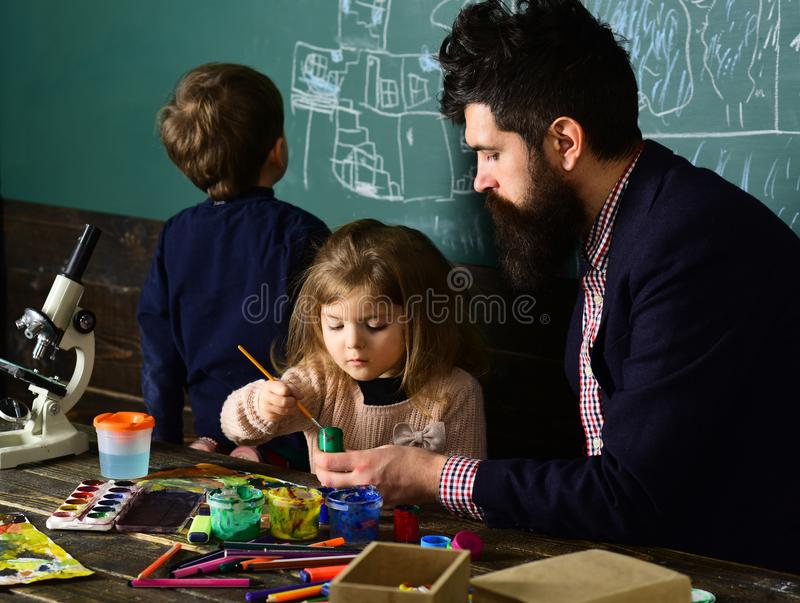 Lesson with qualified private tutor. Kids struggle when they do homework so they need tutor. Teacher helping pupil in stock photo