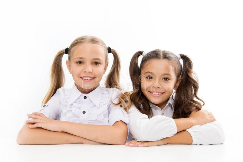 Lesson where learning begins. Cute school children sitting at school desk. Little schoolgirls having lesson at primary. School. Adorable small girls learning royalty free stock photo