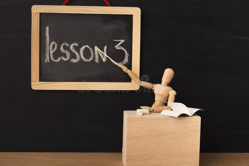 Lesson 3 written with chalk on blackboard. stock photography
