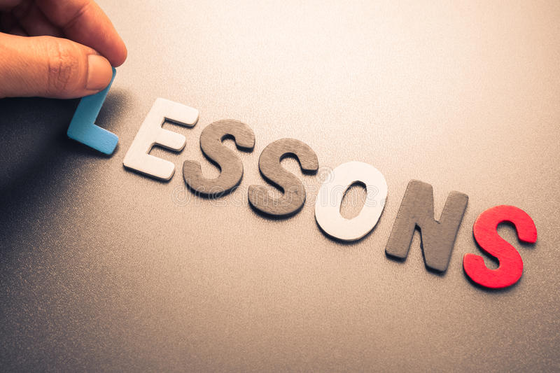 Lessons. Hand arrange wood letters as Lessons Word royalty free stock photography