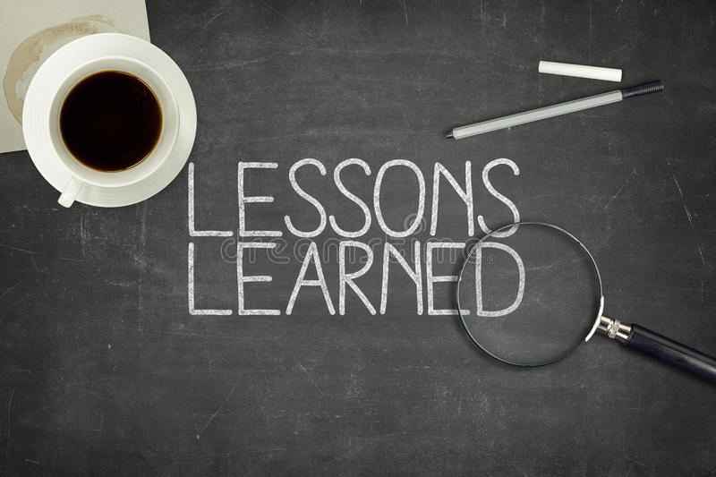 Lessons learned concept on black blackboard. With coffee cupt and paper plane stock photography