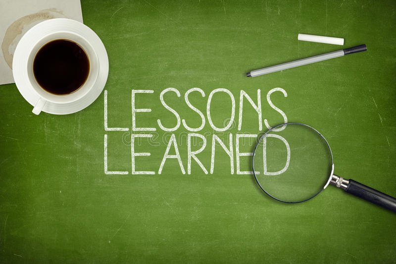 Lessons learned concept on green blackboard. With coffee cupt and paper plane royalty free stock image