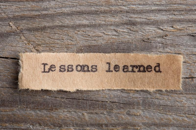 Lessons learned - word on a piece of paper close up, business creative motivation concept. Experience, test, school, knowledge, growing, feedback, comment stock image