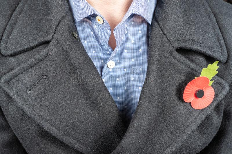 Lest We Forget concept.Remembrance Day 11 November. A poppy is worn on a jacket in tribute to fallen soldiers. Lest We Forget concept. Remembrance Day 11 stock image