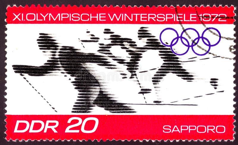 Leste Alemão cerca de 1972: Selo postal cancelado impresso em Leste Alemão, que mostra a competição de esqui olímpica do inverno  imagem de stock