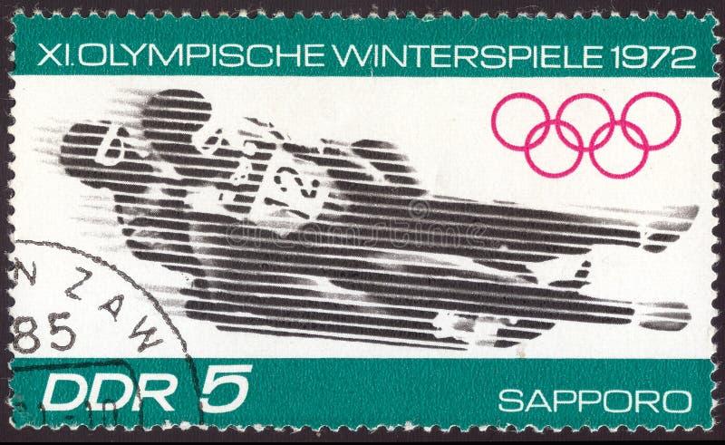 Leste Alemão cerca de 1972: Selo postal cancelado impresso em Leste Alemão, que mostra a competição olímpica do trenó do inverno  fotos de stock royalty free