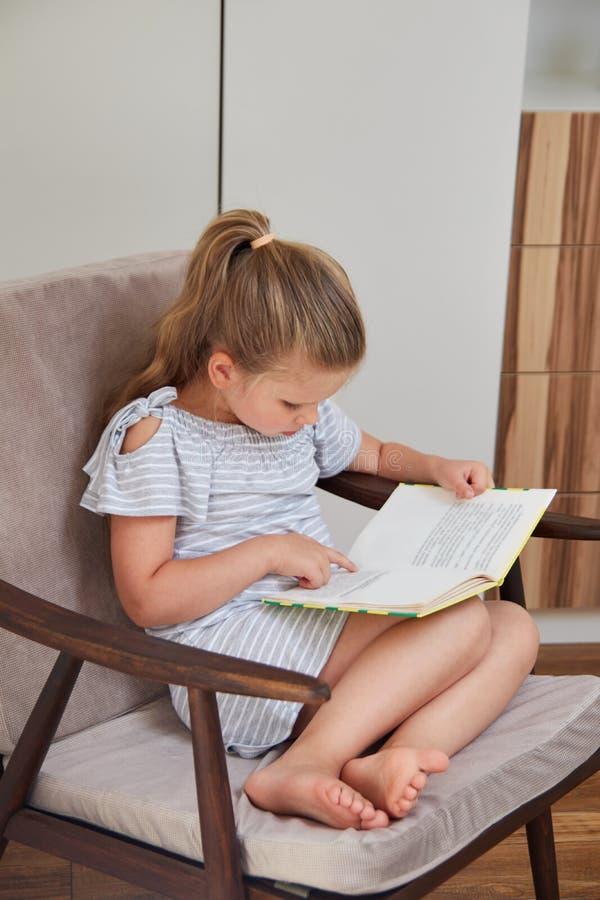 Lesung des kleinen Mädchens, die im Stuhl sitzt stockbilder