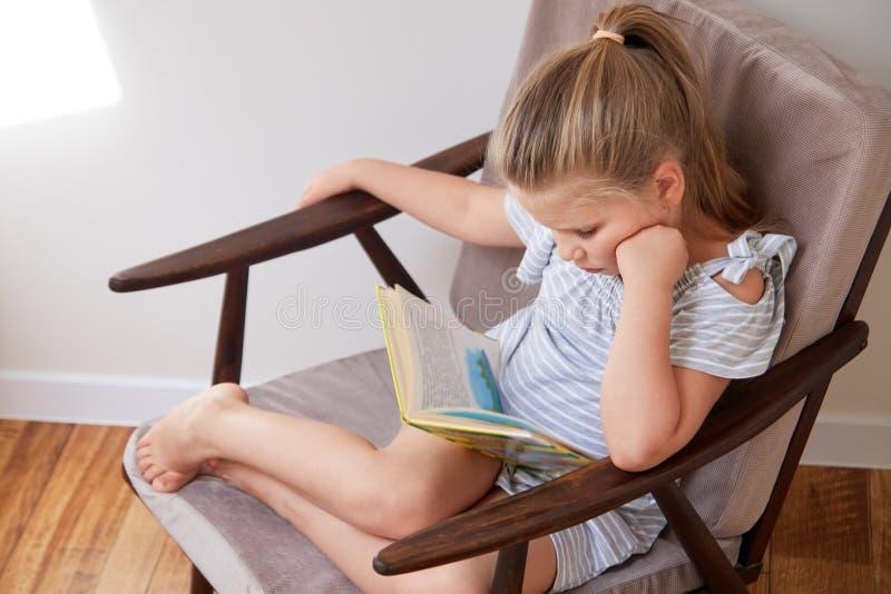 Lesung des kleinen Mädchens, die im Stuhl sitzt lizenzfreie stockfotografie