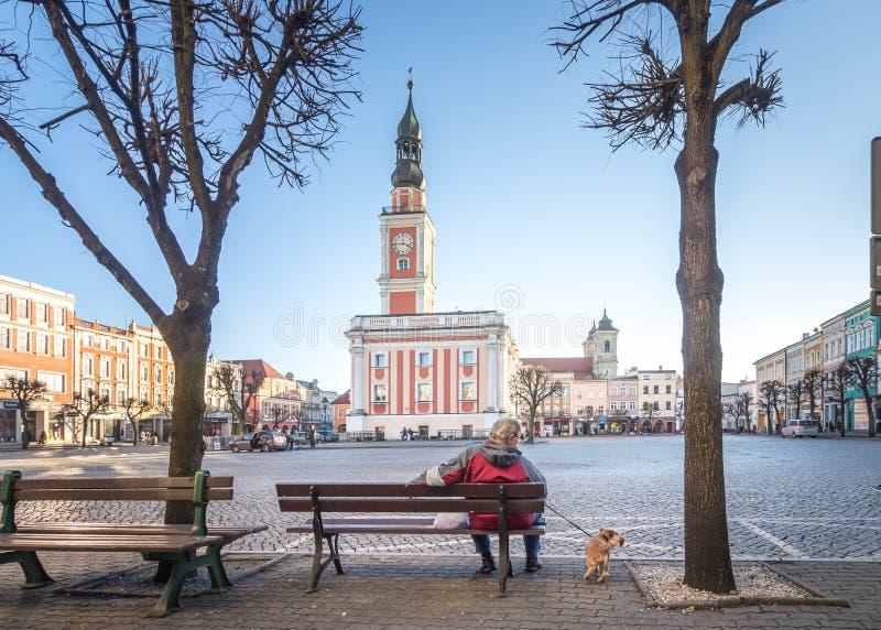 LESZNO POLEN - FEBRUARI 16, 2019 En äldre man med en hund på en ledning som framme sitter på en bänk av det Leszno stadshuset royaltyfria foton