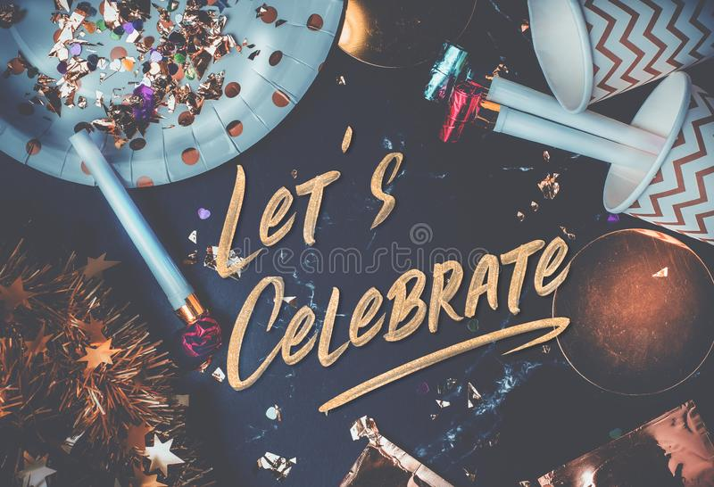 Let's celebrate hand brush stroke font on marble table with party cup,party blower,tinsel,confetti.Fun Celebrate holiday party. Time table top view.blue royalty free stock image