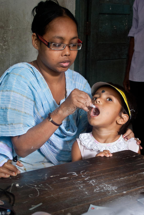 Let's eradicate polio. An Indian woman is giving polio drops to a child at 'Sunday Pulse polio center' in Kolkata, India. Pulse Polio is an immunisation royalty free stock image