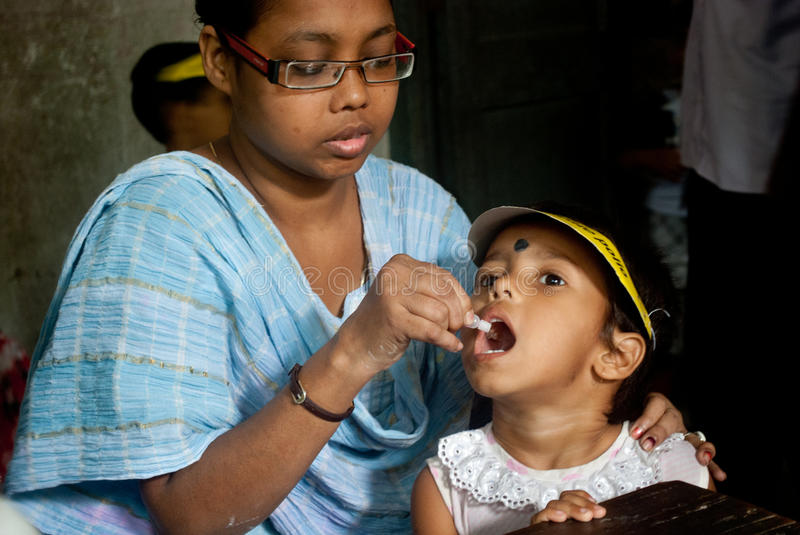 Let's eradicate polio. An Indian woman is giving polio drops to a child at 'Sunday Pulse polio center' in Kolkata, India. Pulse Polio is an immunisation stock photography