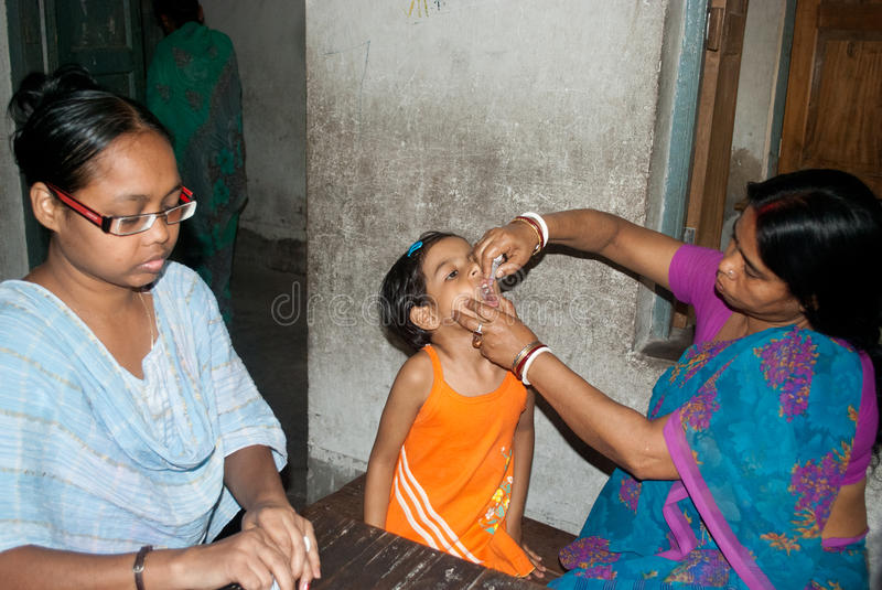 Let's eradicate polio. An Indian woman is giving polio drops to a child at 'Sunday Pulse polio center' in Kolkata, India. Pulse Polio is an immunisation royalty free stock photography