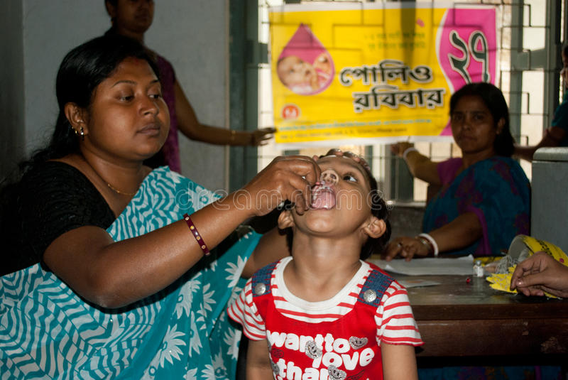 Let's eradicate polio. An Indian woman is giving polio drops to a child at 'Sunday Pulse polio center' in Kolkata, India. Pulse Polio is an immunisation stock images