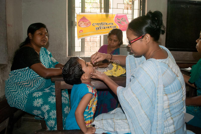 Let's eradicate polio. An Indian woman is giving polio drops to a child at 'Sunday Pulse polio center' in Kolkata, India. Pulse Polio is an immunisation stock photos