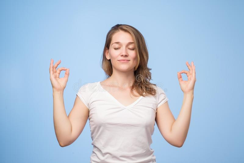 Let be calm. Portrait of focused relaxed attractive female with closed eyes, happy smile, meditating with spread hands royalty free stock photography