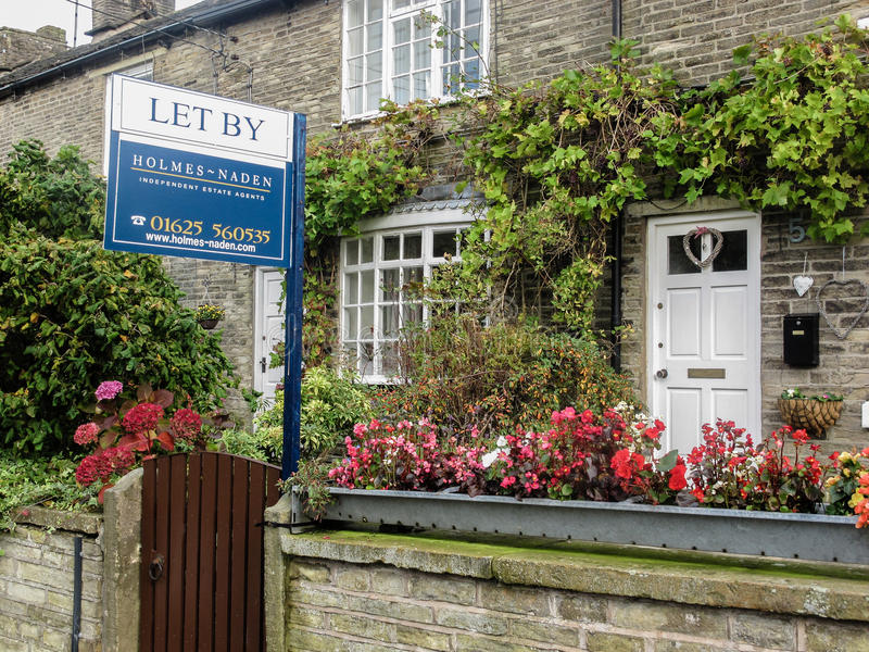 Let-by estate agent board in front of a traditional stone country cottage stock photography