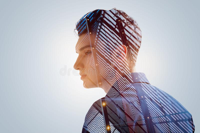 Creative freedom inaccessible for young talented guy. Let me go. Sad pensive young man dreaming about freedom while standing in profile and looking down royalty free stock photography