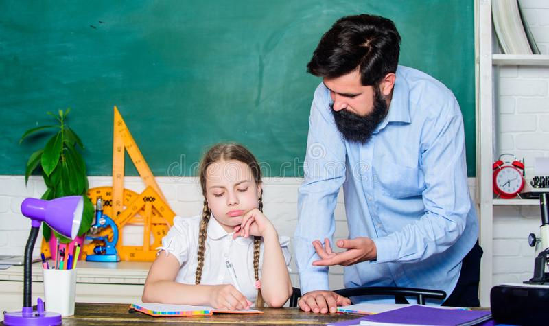 Let me help you. bearded man teacher with small girl in classroom. daughter study with father. Teachers day. education. Let me help you. bearded men teacher with stock image