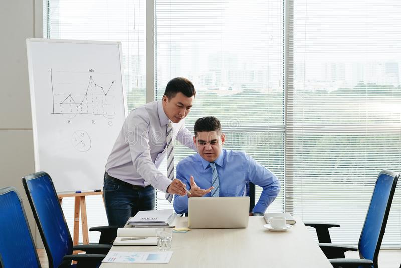 Let me help you. Vietnamese businessman helping his coworker with work stock photos