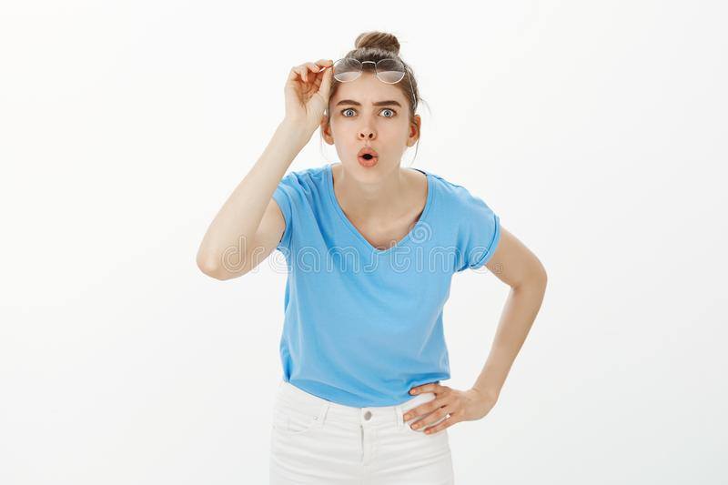 Let me look closer. Portrait of intrigued attractive female scientist, taking off glasses, bending towards camera with royalty free stock image