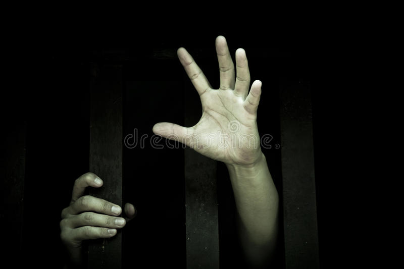 Let me out. Human hand stretch out from prison bars stock images