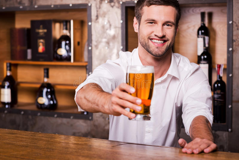 Let me quench your thirst!. Happy young male bartender in white shirt stretching out glass with beer and smiling while standing at the bar counter stock photography