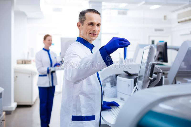 Resolute happy researcher reading label on the test tube royalty free stock photos