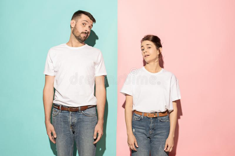 Let me think. Doubtful pensive couple with thoughtful expression making choice against pink background stock image