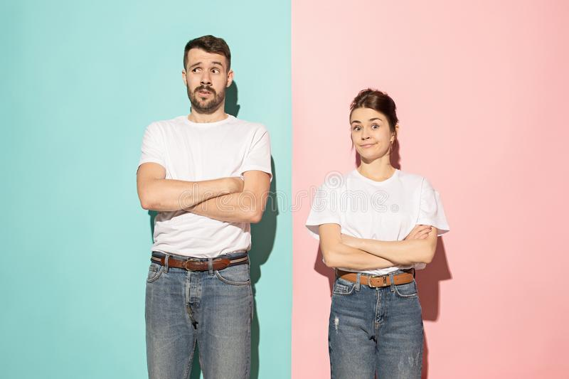 Let me think. Doubtful pensive couple with thoughtful expression making choice against pink background royalty free stock photos