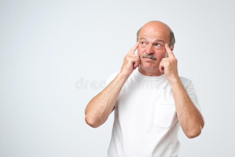 Isolated portrait of puzzled senior male looking up and holding fingers on his temples, trying to remember something royalty free stock photography