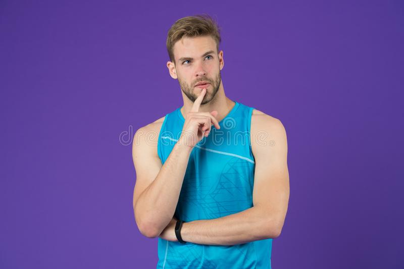 Let me think. Man with strong muscular arms. Man muscular handsome unshaven thoughtful guy on violet background. Masculinity concept. Does having muscular body stock photo