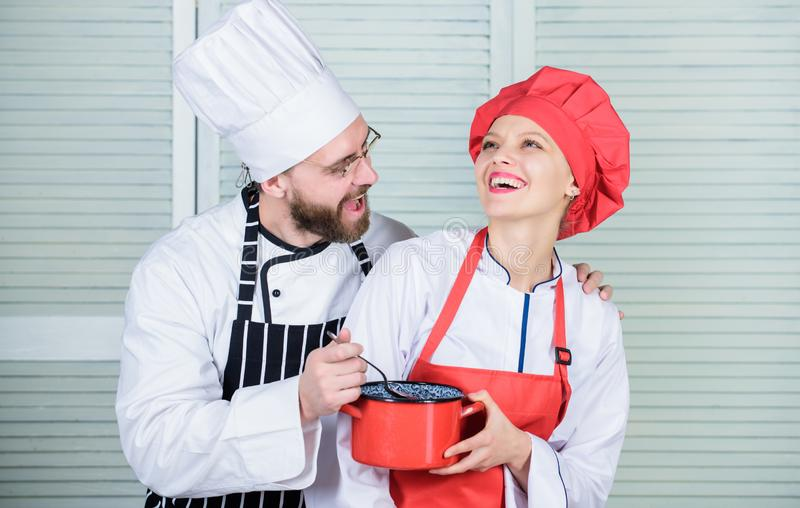 Let my try taste. Couple having fun while whipping cream. Woman and bearded man chef cooking together. Cooking healthy. Let my try taste. Couple having fun while stock photos