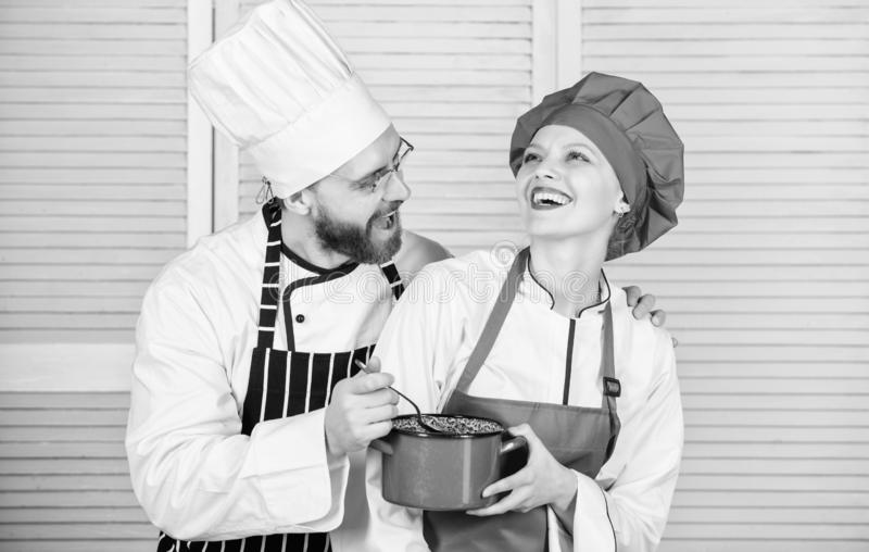 Let my try taste. Couple having fun while whipping cream. Woman and bearded man chef cooking together. Cooking healthy. Let my try taste. Couple having fun while stock photo
