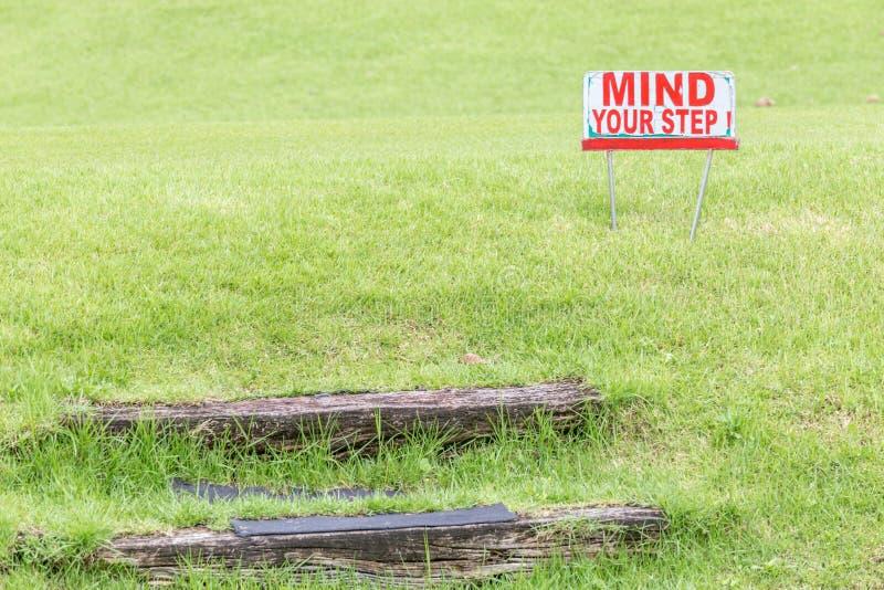 Let op uw stapwaarschuwingsbord om van natuurlijke houten stappen te alarmeren royalty-vrije stock afbeeldingen