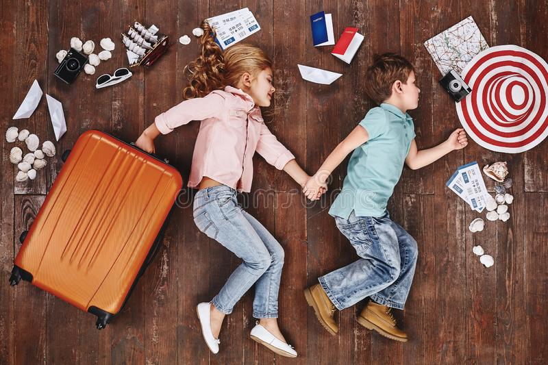 Let`s be adventurers. Children lying near travel items. Girl with suitcase stock image