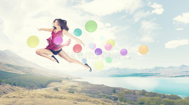 Let's celebrate. Young cheerful lady in red dress jumping high stock photos
