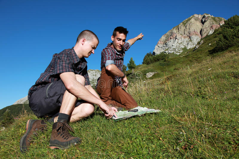 Let's climb on the mountain!. Two young backpackers want to climb on a mountain royalty free stock photos