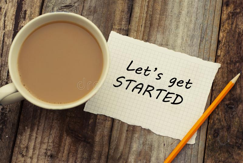 Let& x27;s get started inscription on white blank papper. Cup of coffee and pencil, over rustic wooden background. stock photography