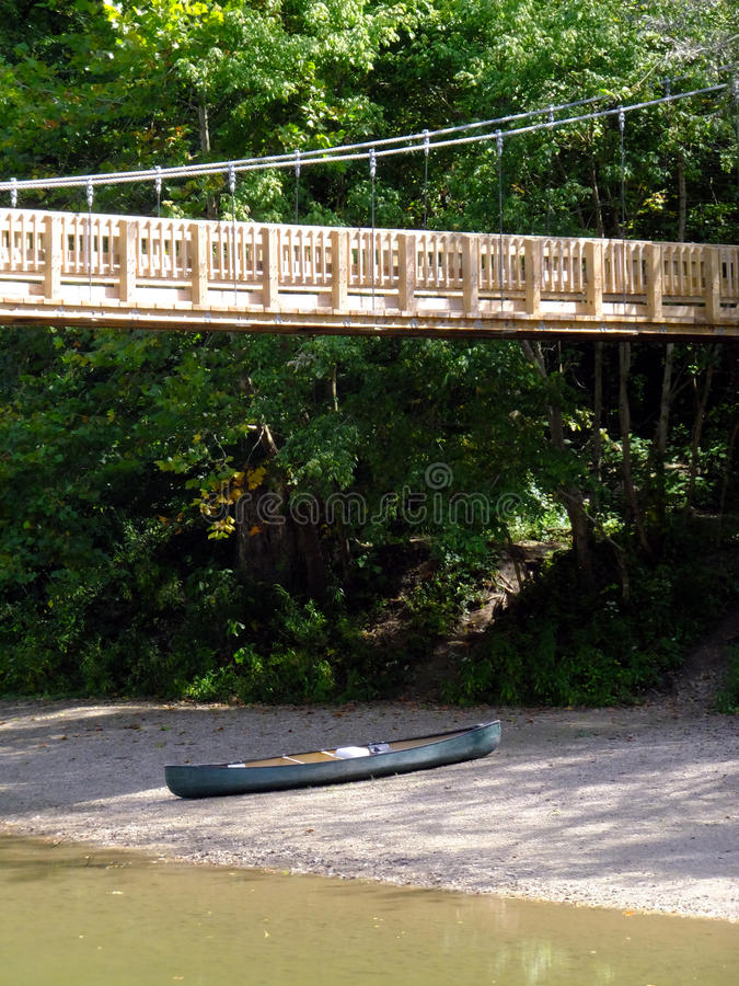 Let's Go. Canoe under suspension bridge awaiting departure royalty free stock images