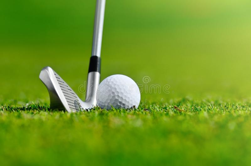 Let`s golf today. Close up of a golf ball and iron on the grass stock photos