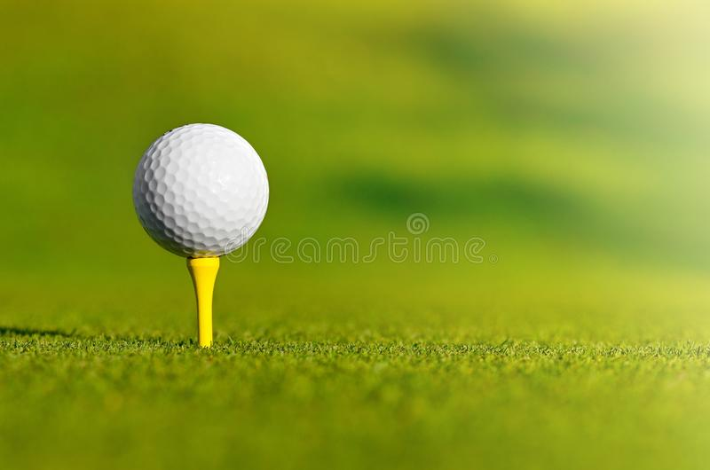 Let`s golf today!. Close up of a golf ball on a yellow tee stock photography