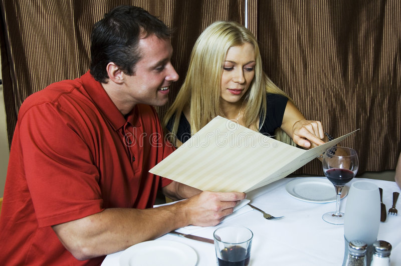 Let's have this!. Happy young couple, deciding what to order in order to start their romantic dinner