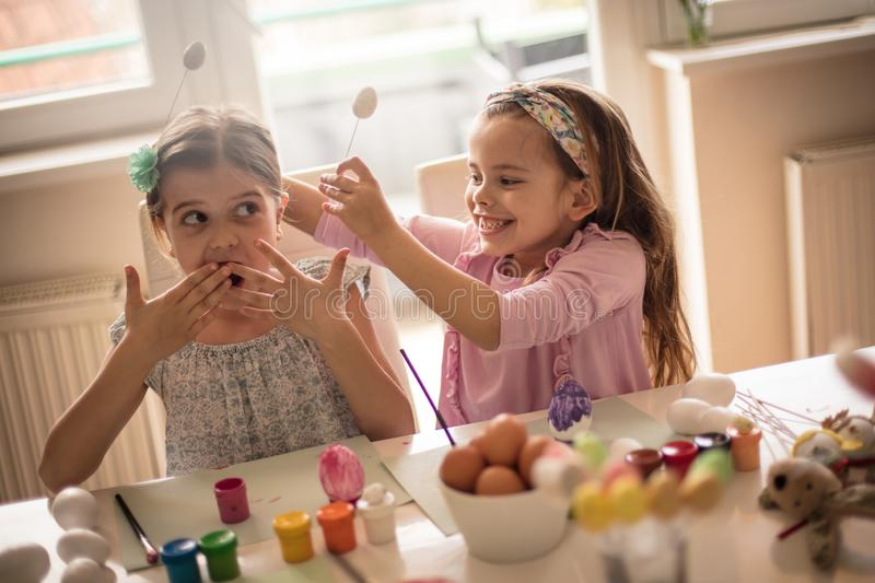 Let`s have fun, it`s Easter. Little girls coloring Easter egg royalty free stock photos